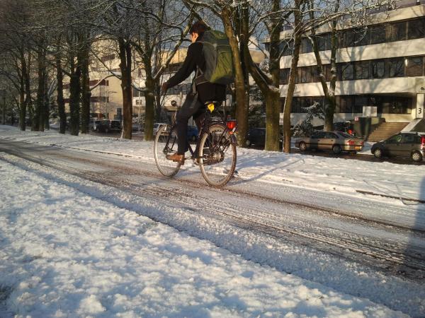 Fietser glibbert over fietspad met sneeuw en ijs