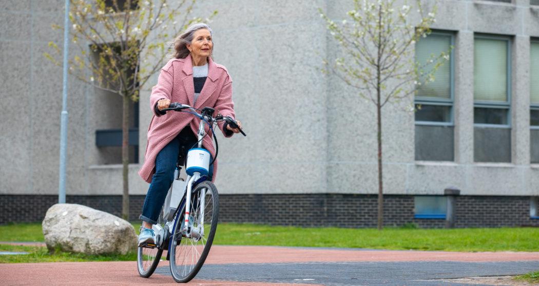 Vrouw op fiets met stuurhulp