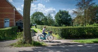 Een meisje fietst op het Groningse platteland