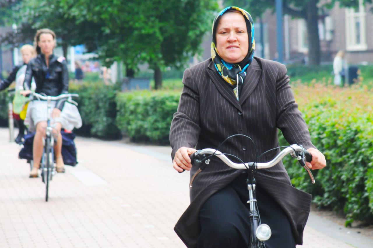 Vrouw met hoofddoek fietst in Amsterdam