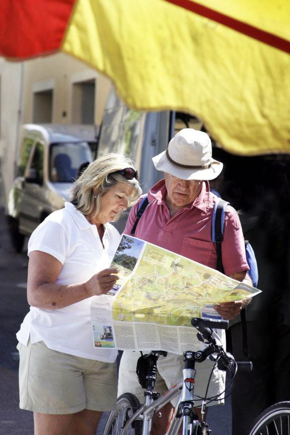 Gepensioneerd echtpaar leest de routekaart tijdens een fietstocht