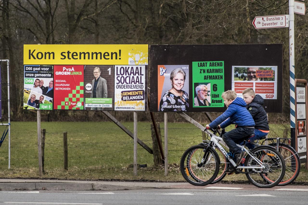 Kinderen fietsen langs een verkiezingsbord in Klarenbeek.