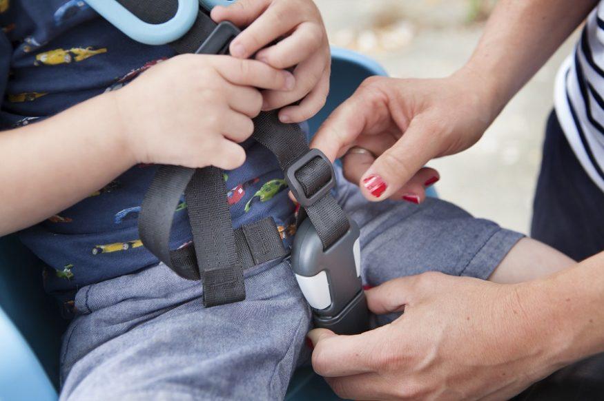 Vastmaken van kind met gordel in kinderzitje