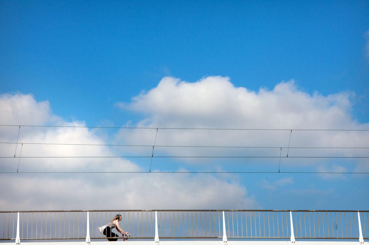 Vrouw fietst op brug in Rotterdam met wolken