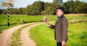 Man in historisch pak staat met een oude reisgids in landschap