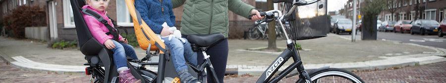Vrouw met twee kinderen op Azor tweelingfiets