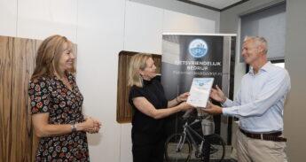 Max Mooij van de Fietsersbond (r) reikt het certificaat uit aan Joke Boonstra van het Erasmus MC. Links de Rotterdamse wethouder Judith Bokhove.