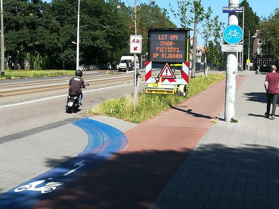 Scooter rijdt over blauwe strook naar de rijbaan