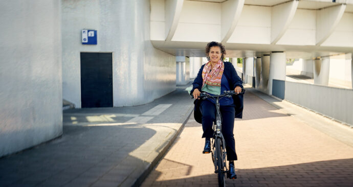 Vrouw fietst onder sporen door