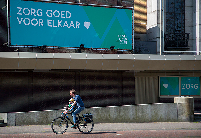 Man fietst langs corona-spandoek in Arnhem
