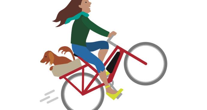Vrouw met hondje rijdt fluitende de heuvel op dankzij haar e-bike