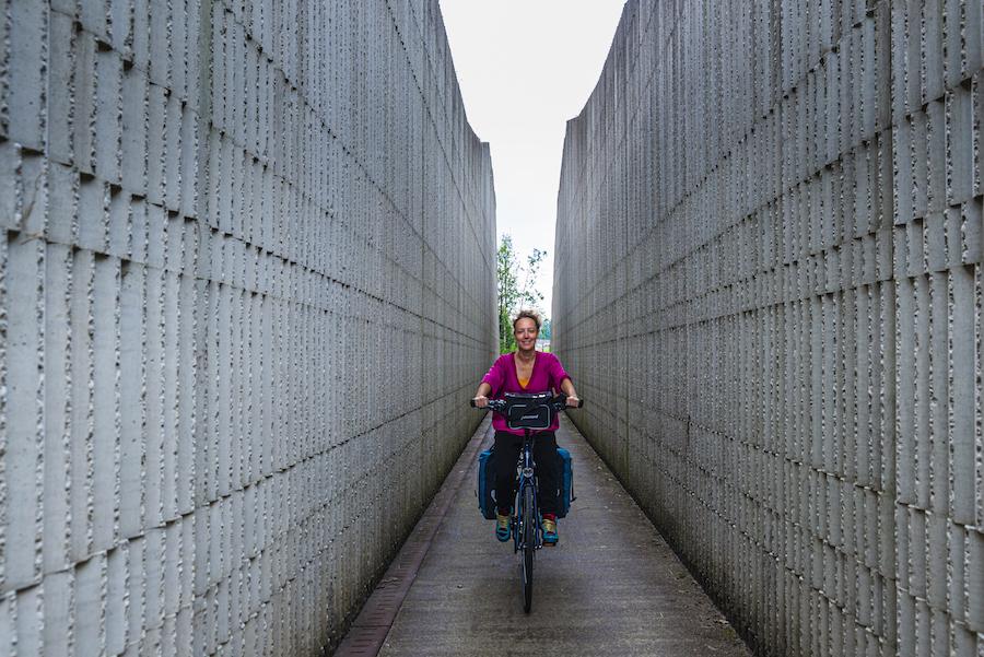 Vrouw fietst tussen twee muren door bij Fort bij Vechten