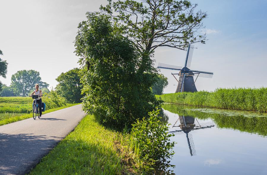 Vrouw fietst langs rivier met molen op de achtergrond