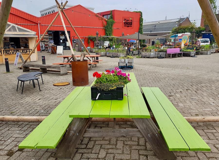 Groene picknichtafel voor rood gebouw met houten plantenbakken