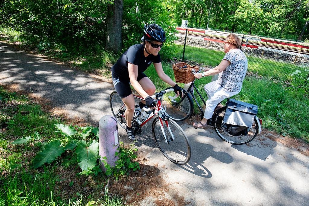 Een wielrenner en een vrouw op een stadsfiets ontwijken elkaar op een fietspad tussen Soest en Den Dolder door het bos.