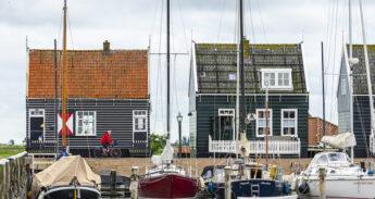 Man fietst door Marken langs boten en huisjes