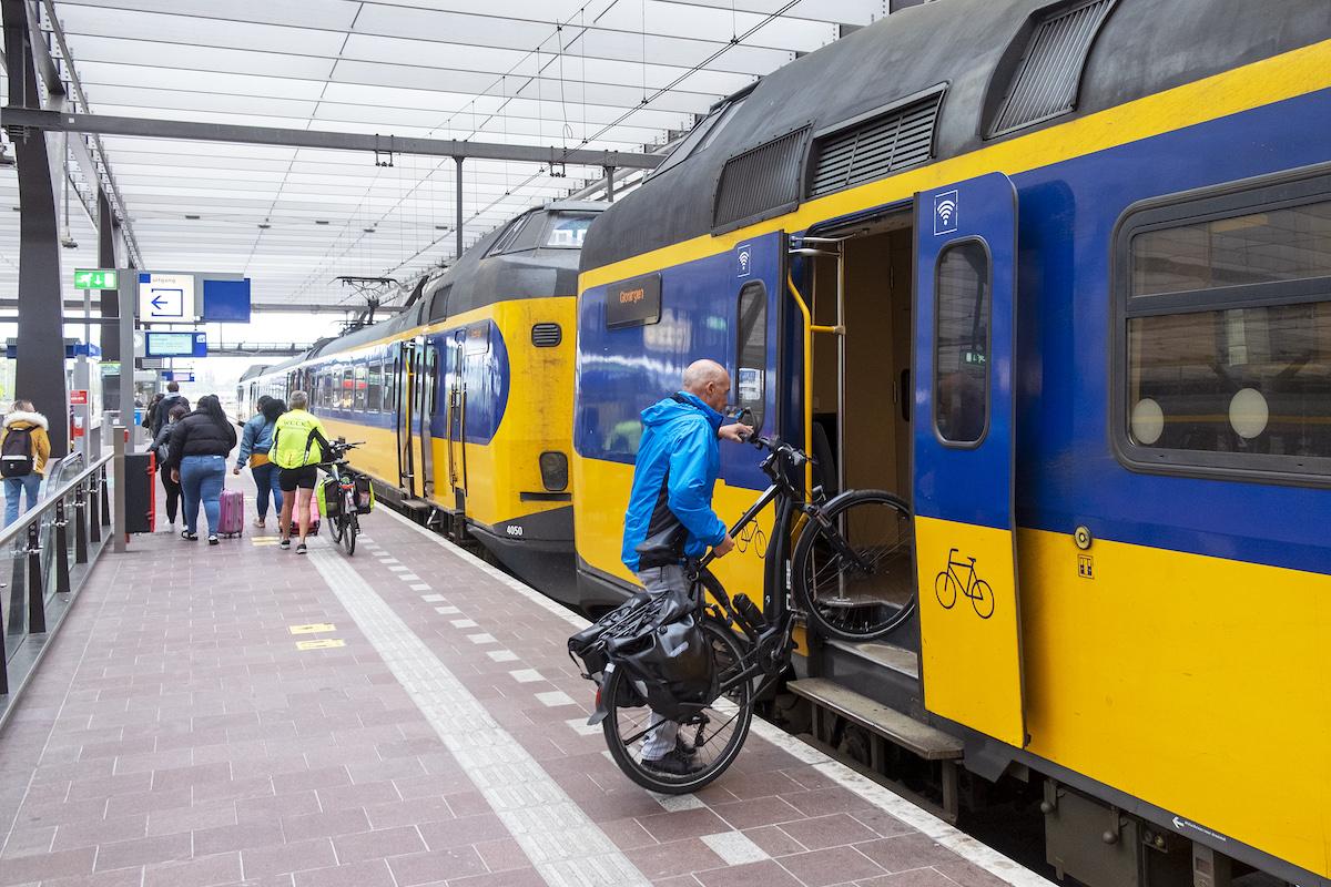 Man tilt fiets in trein