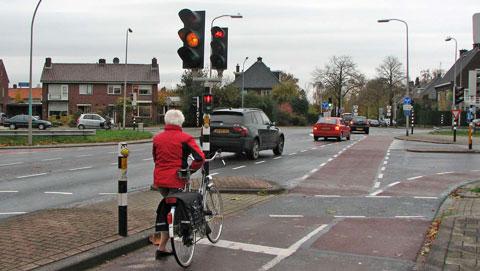 fietser voor rood stoplicht. voor auto's oranje