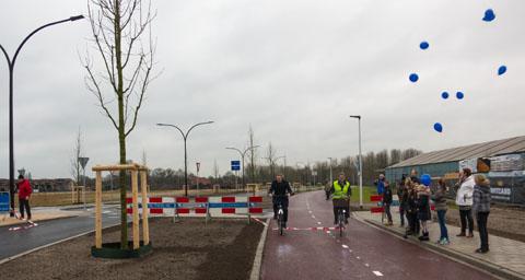 Twee fietsers openen het fietspad en scholieren laten ballonnen op.
