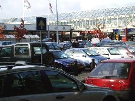 Ingang winkels ergens achter het parkeerterrein