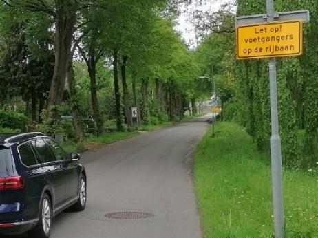 Foto 1: voetgangers, fietsers en auto's delen de rijweg