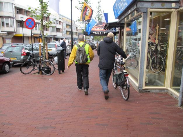 Een fietser wordt naar de werkplaats begeleid..