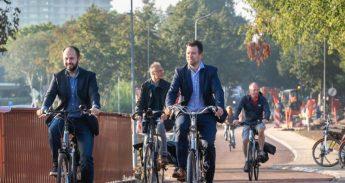 wethouders fietsen over de nieuwe brug